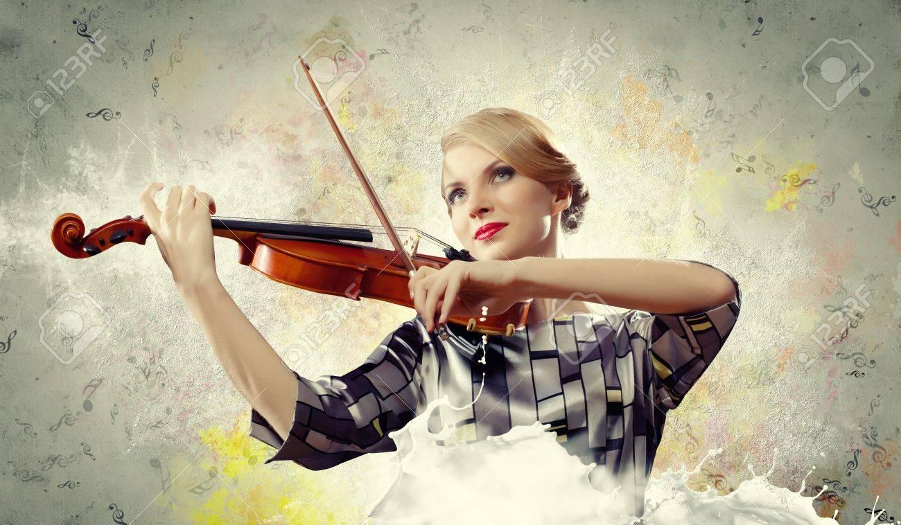 Image of beautiful female violinist playing against splashes background Stock Photo - 17672548