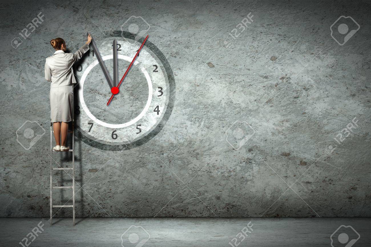 Businesswoman standing on ladder moving hands of clock Stock Photo - 18472190