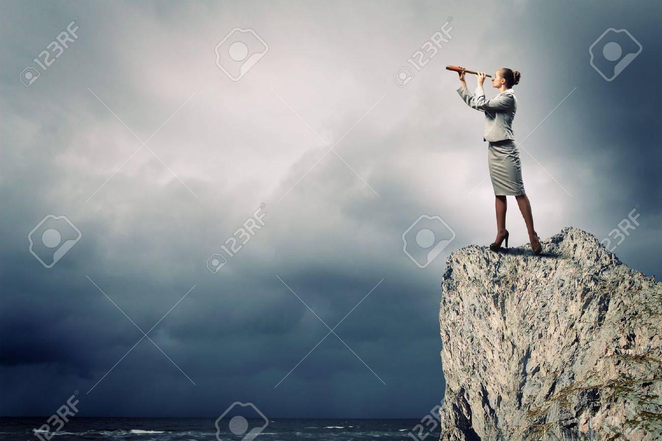 Image of businesswoman looking in telescope standing atop of rock - 18560442