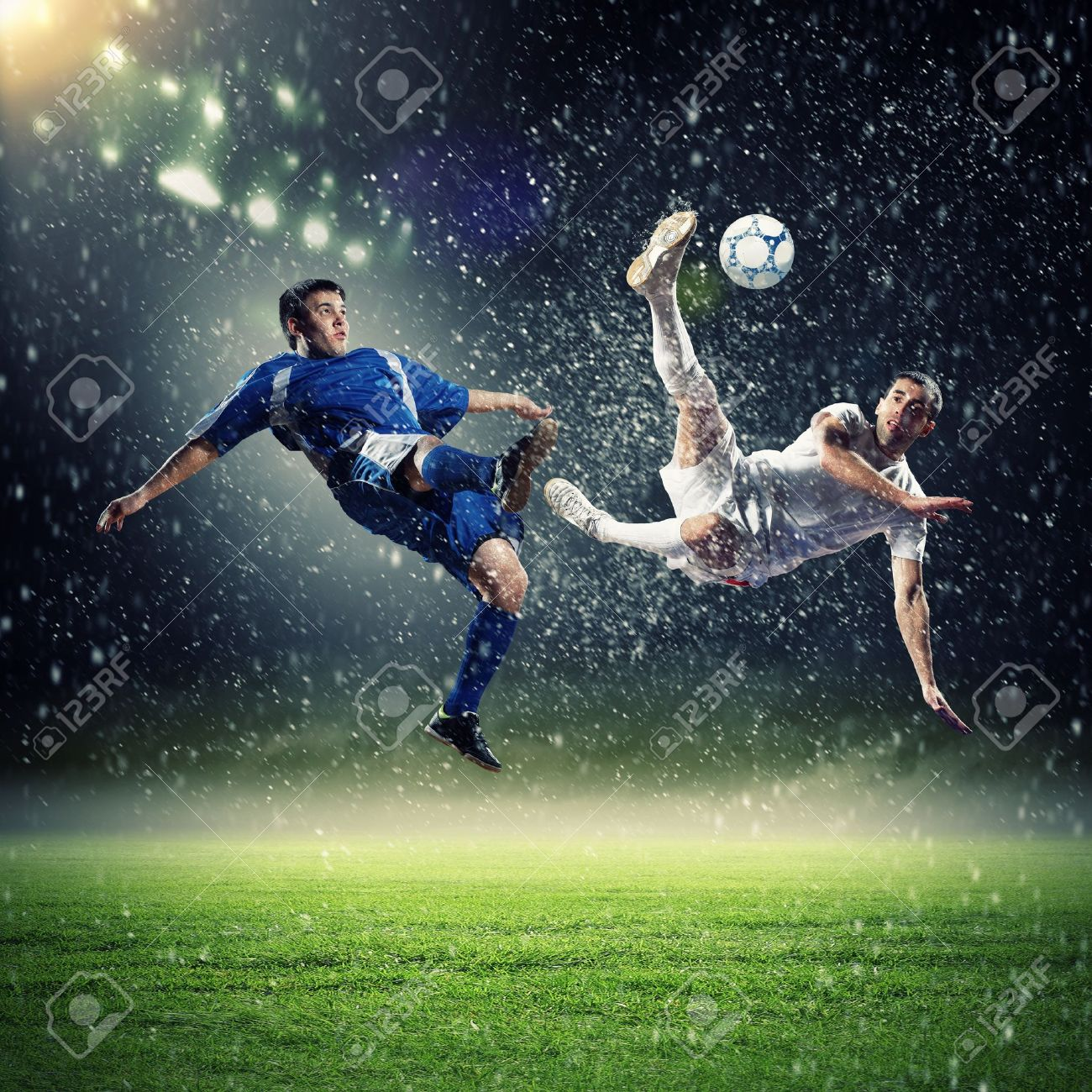 two football players in jump to strike the ball at the stadium under rain Stock Photo - 19206214