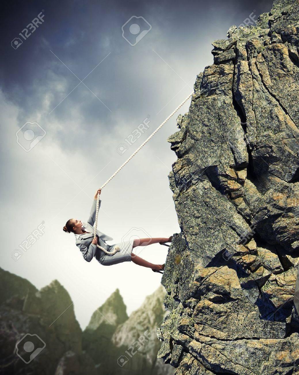 businesswoman climbing steep mountain hanging on rope Stock Photo - 20026179