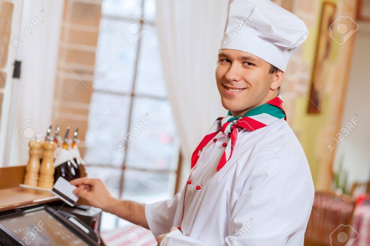 Image of handsome chef inserting card in terminal Stock Photo - 20236597