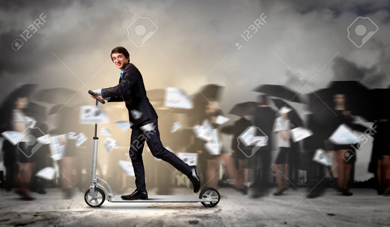 Image of young businessman in black suit riding scooter Stock Photo - 20327159