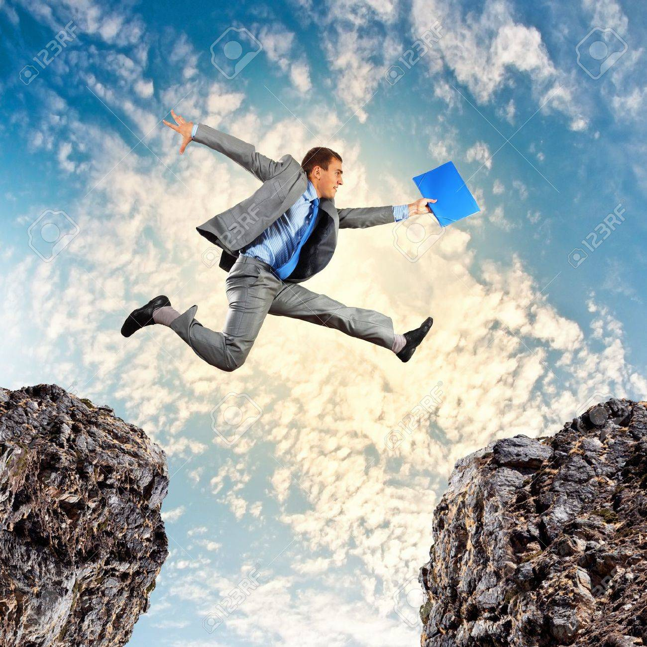 Image of young businessman jumping over gap Stock Photo - 20327511