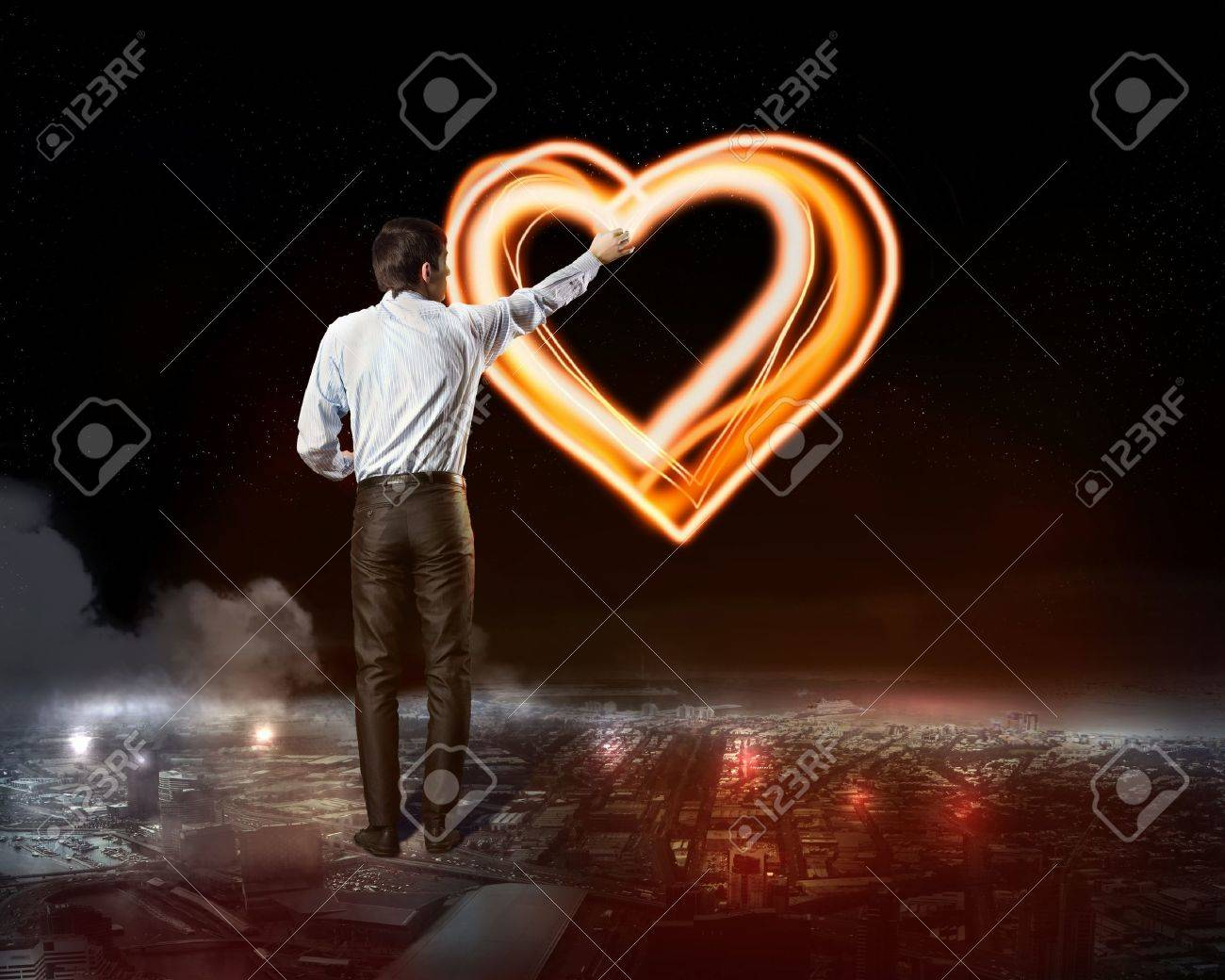 Businessman draws a glowing signs in the dark sky Stock Photo - 20382967