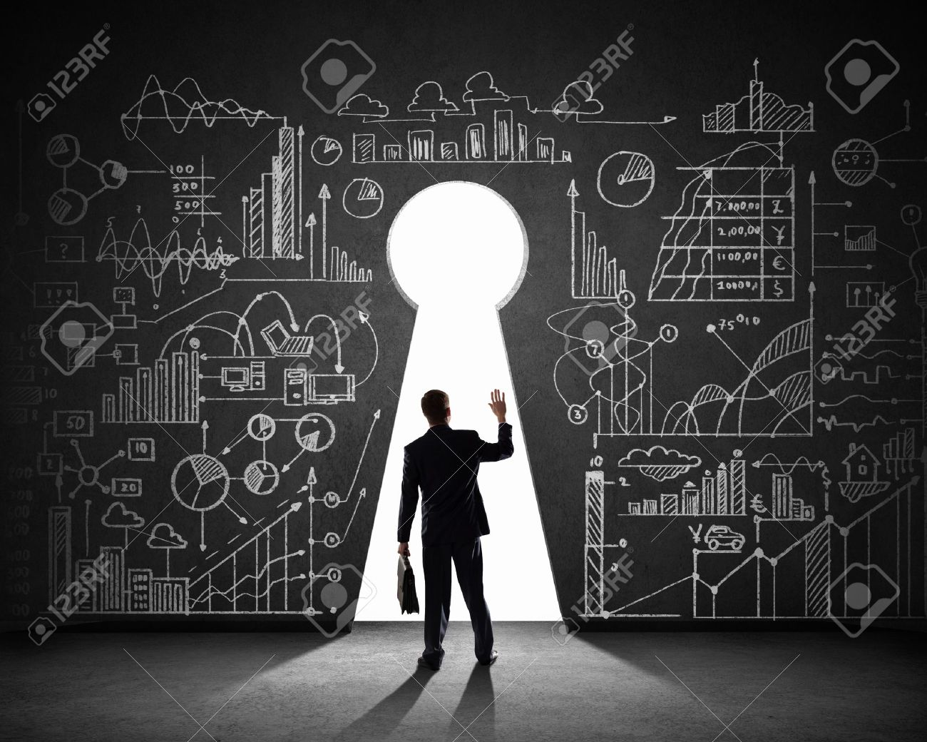 Silhouette of businessman against black wall with key hole - 21644034