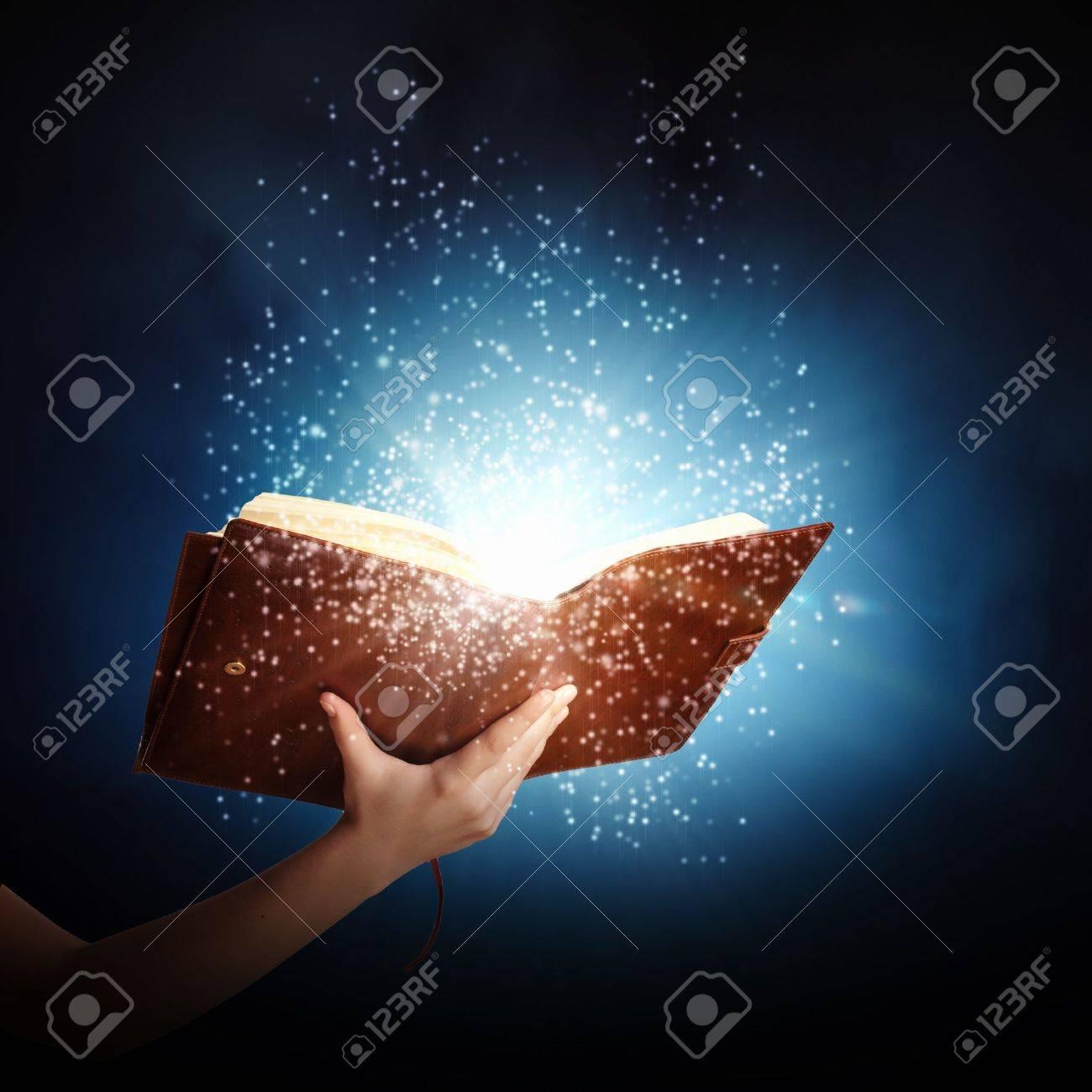 Human hand holding magic book with magic lights Stock Photo - 22040066