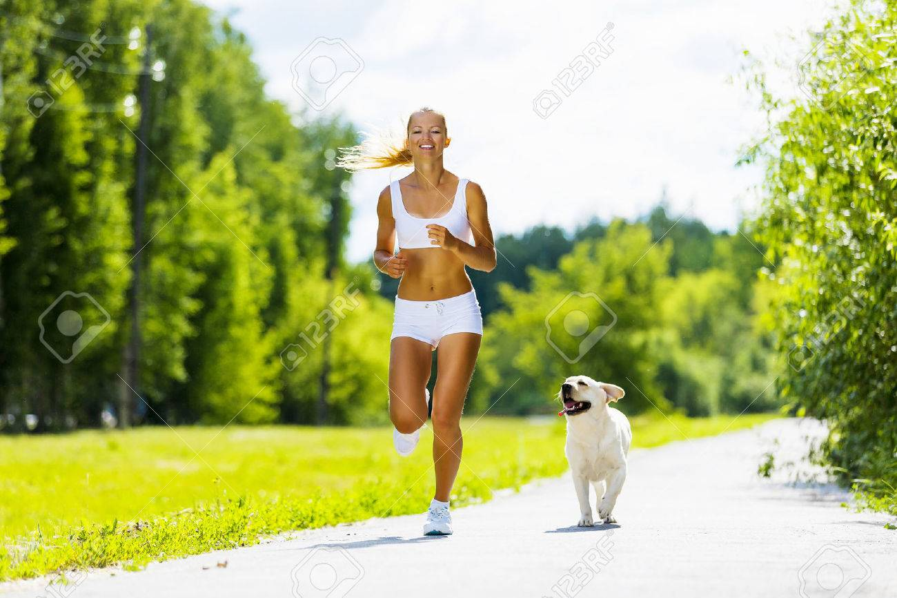 young attractive sport girl running with dog in park stock photo