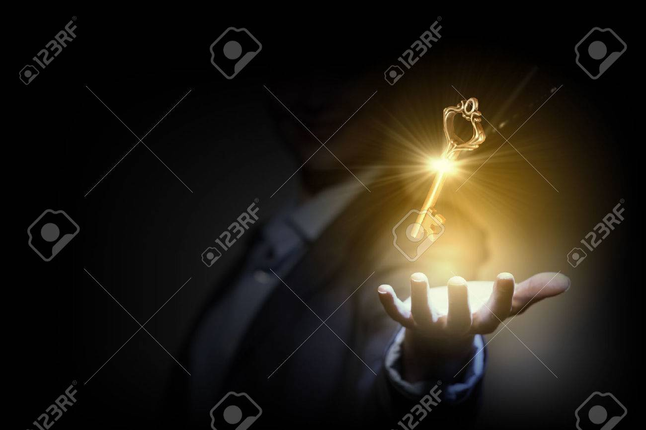 Close up image of business person holding shining key - 30572678