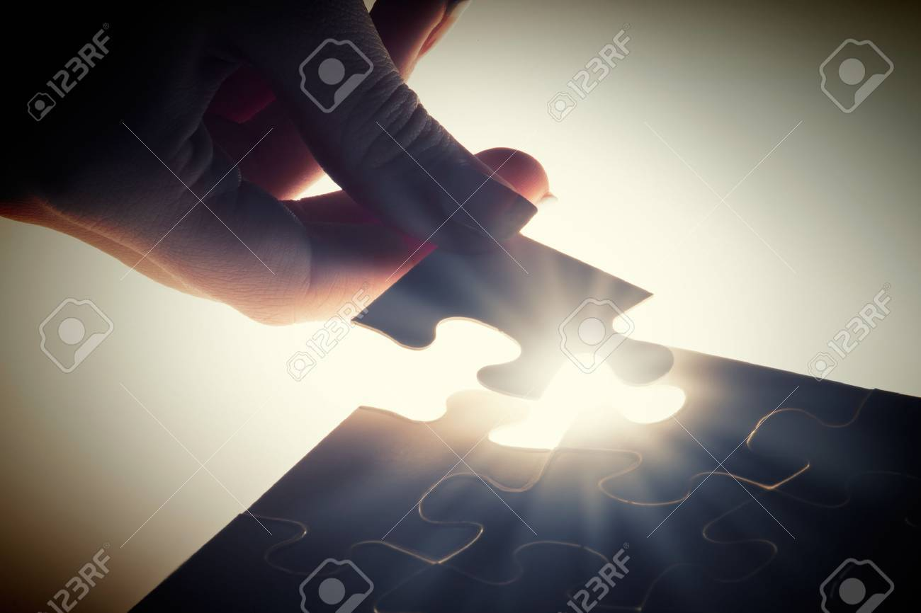 Close up of hands connecting puzzle element and making jigsaw complete - 42138862