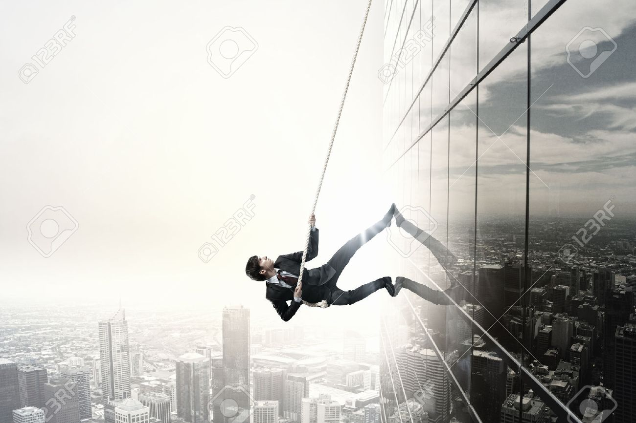 Concept of competition with businessman climbing office building with rope - 42327838
