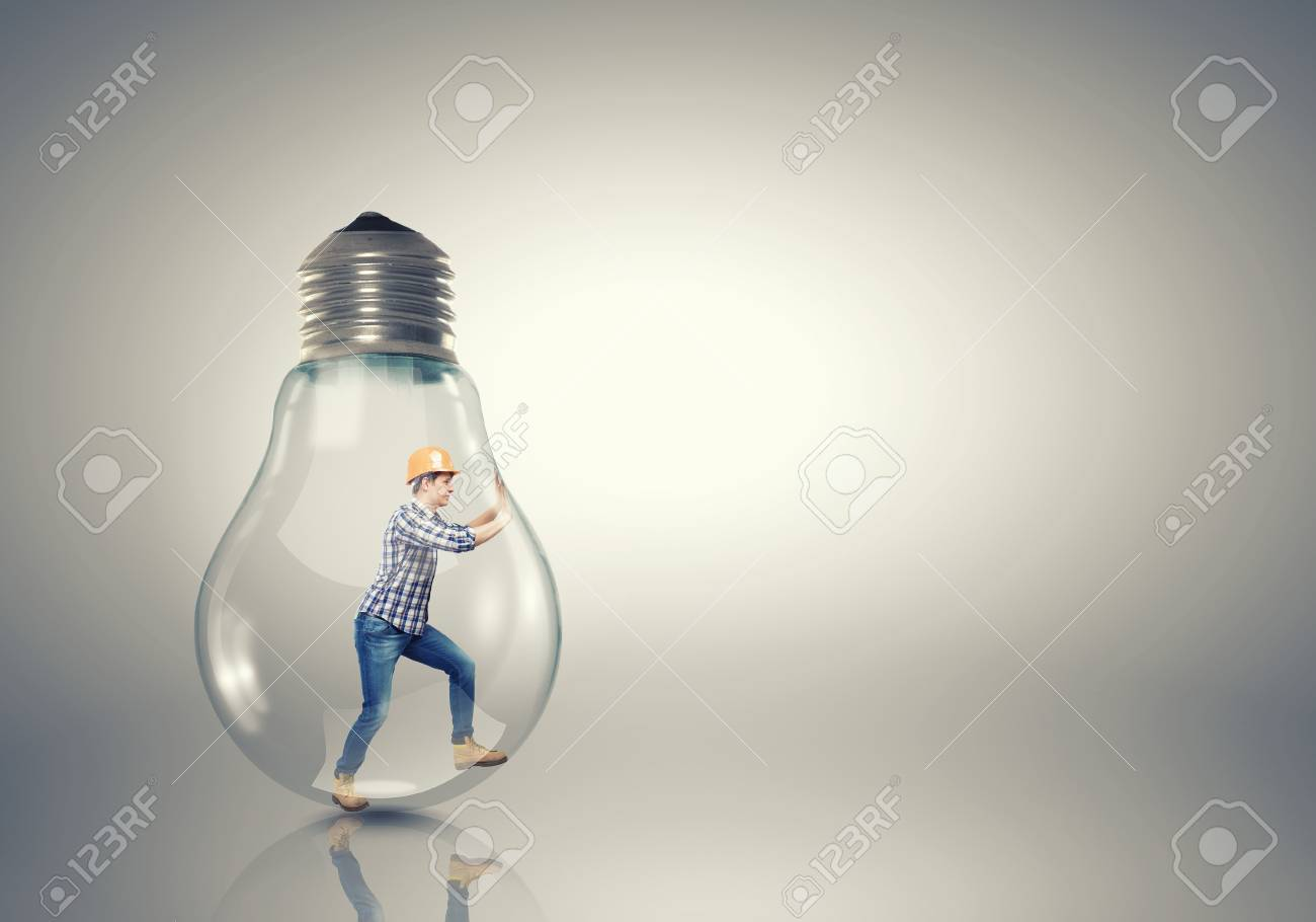 builder man inside light bulb trying to get out stock photo picture