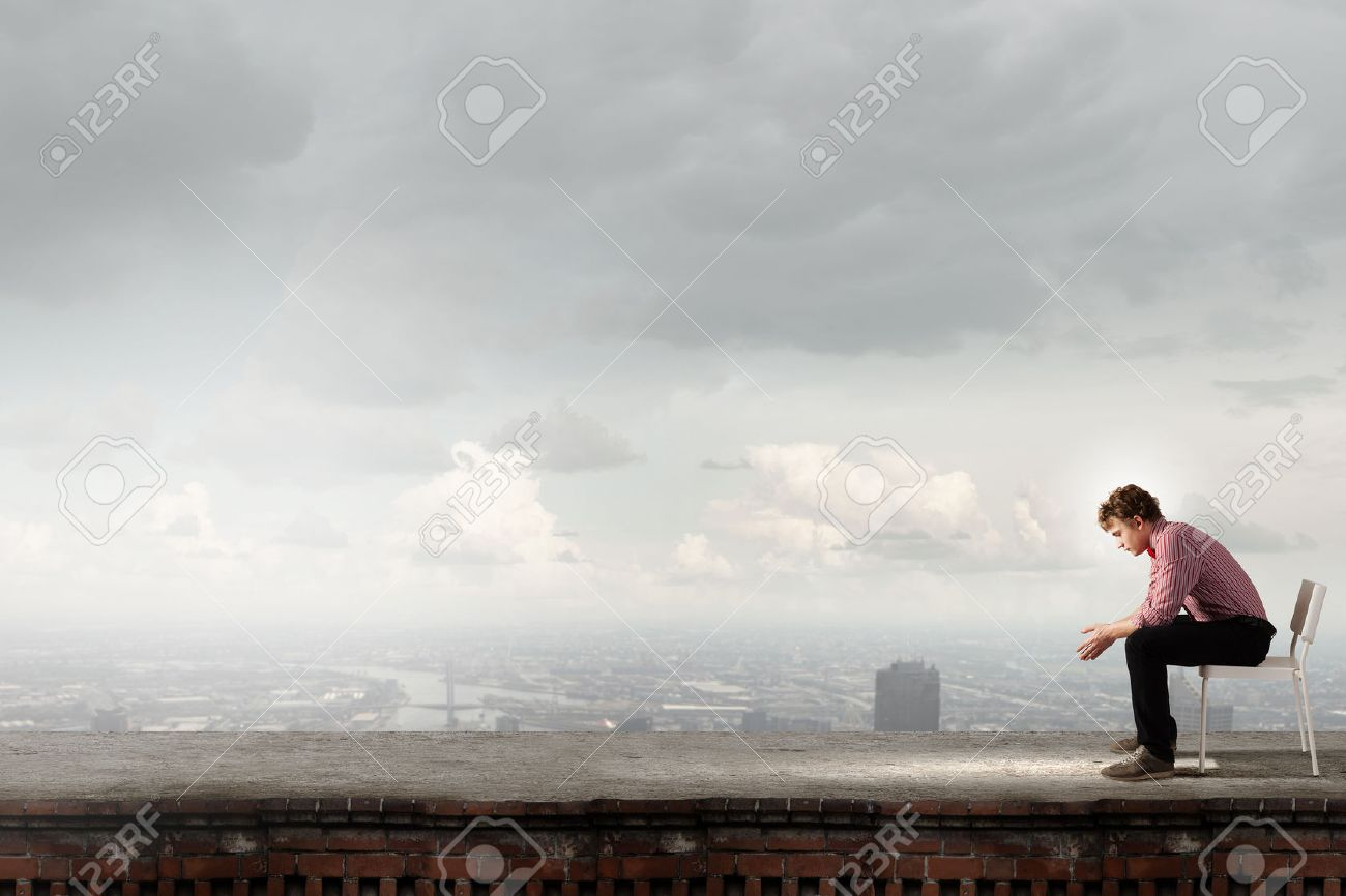 Depressed man sitting on a chair all alone Stock Photo - 45034200