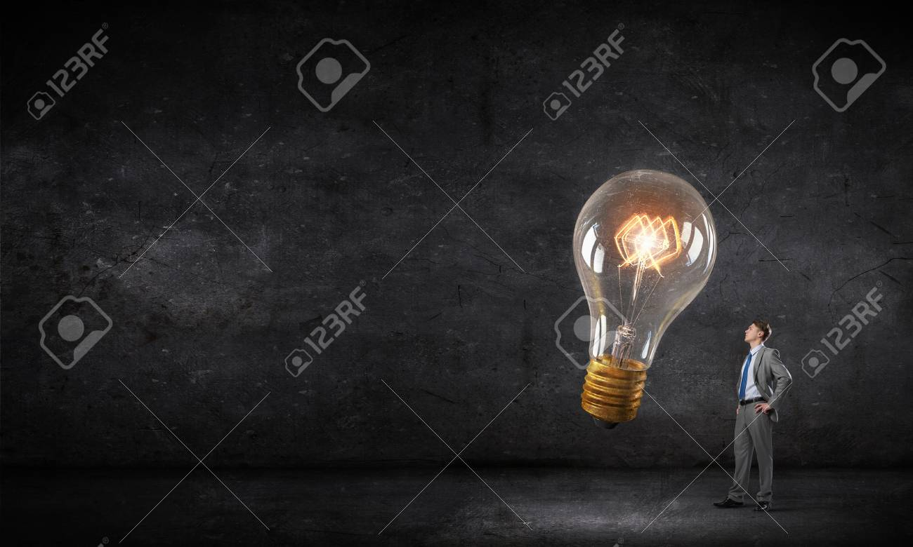 Young businessman in darkness looking at glowing light bulb - 50267779