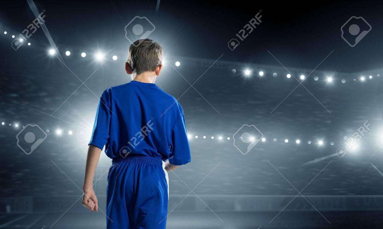 Rear view of kid boy in blue uniform on soccer stadium Stock Photo - 50598011