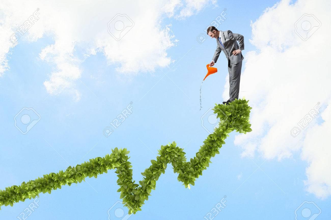 Jeune homme d'affaires gaie arrosage vert graphique de croissance can Banque d'images - 52699505