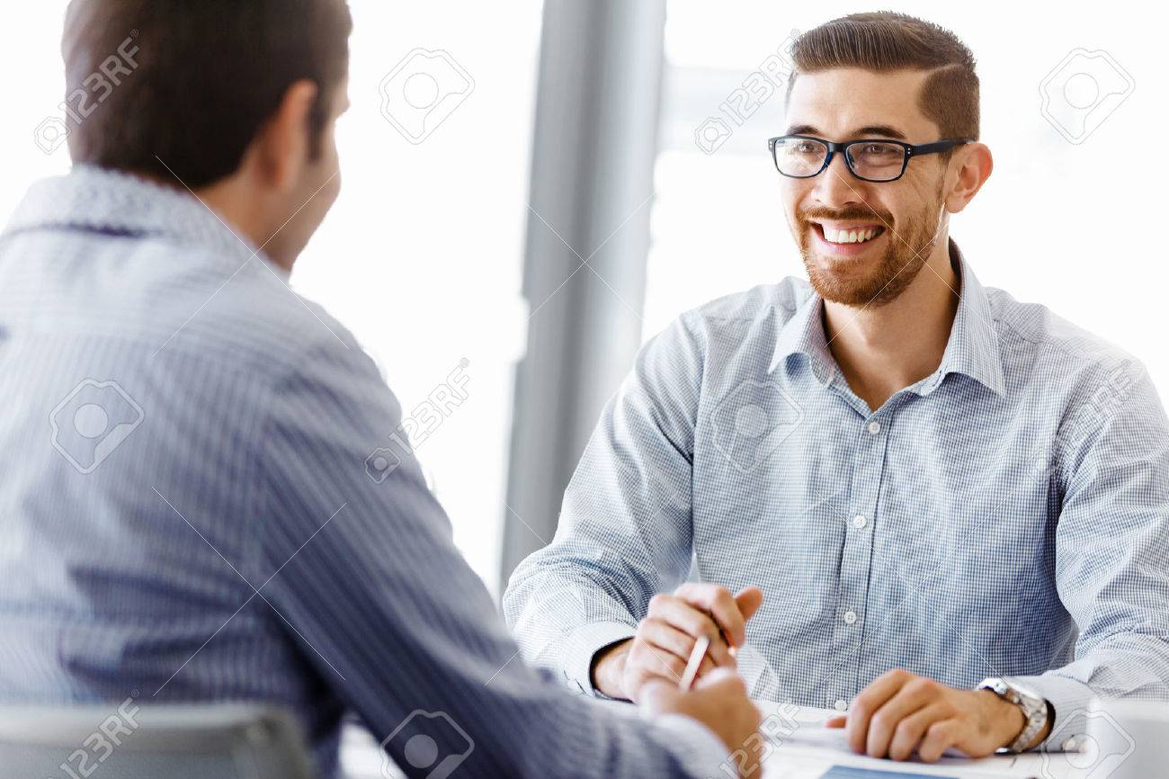 Two handsome businessman in office sitting at desk and talking Stock Photo - 52766054
