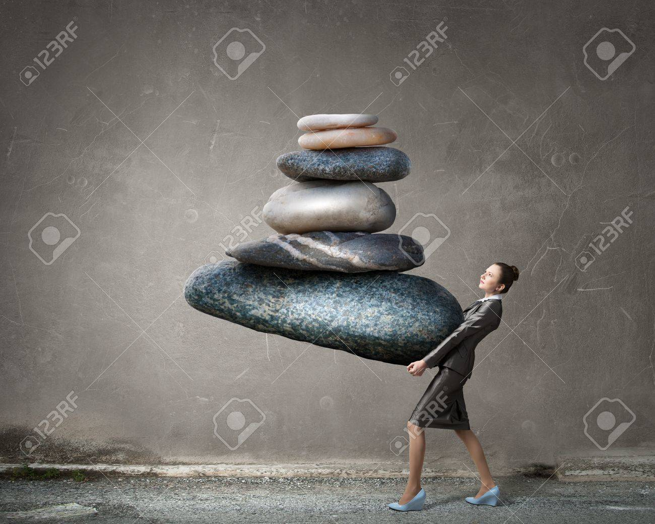 Attractive businesswoman carrying stack of stones in hands Standard-Bild - 52850787