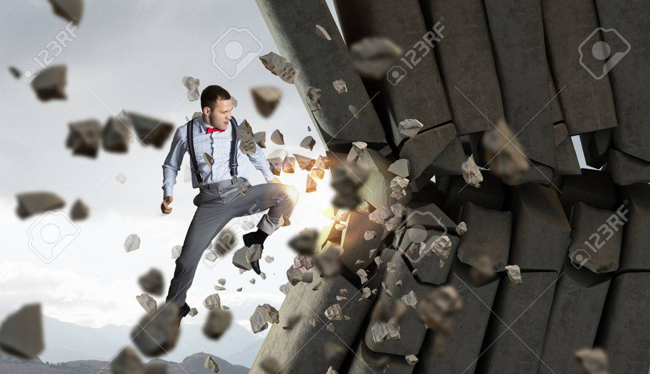 determined businessman breaking stone bricks with hand punch stock