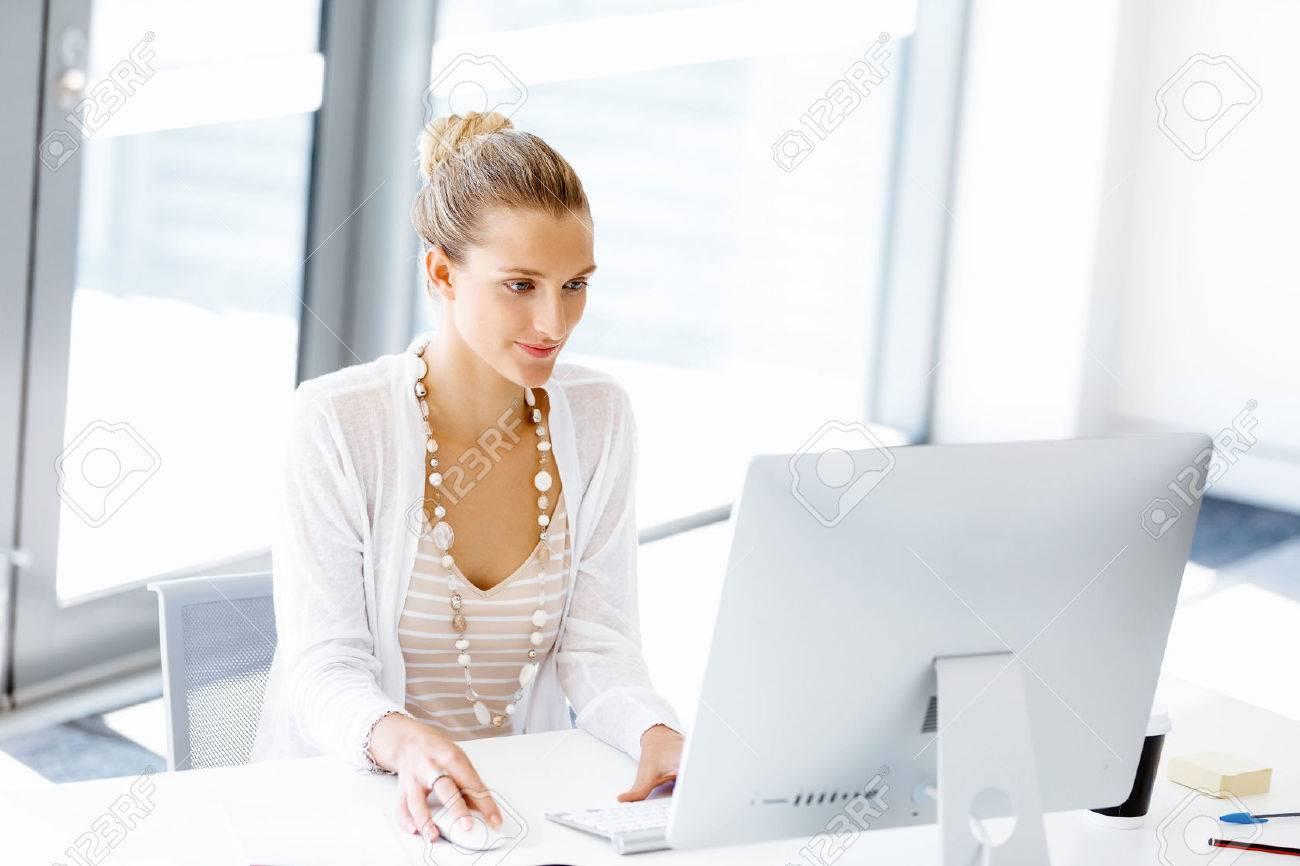 Attractive femme assise au bureau dans le bureau Banque d'images - 54334524