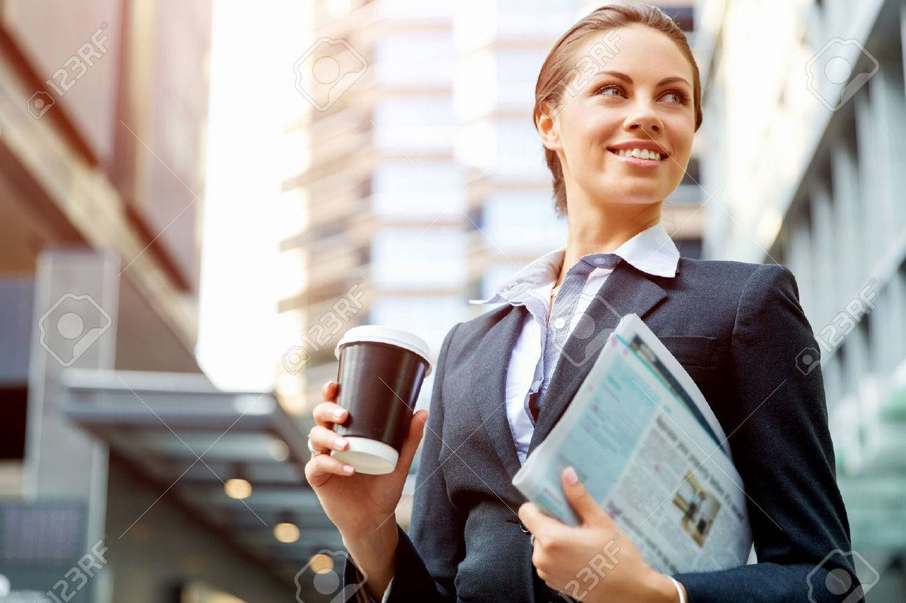 Portrait of young business woman walking in city - 54535324