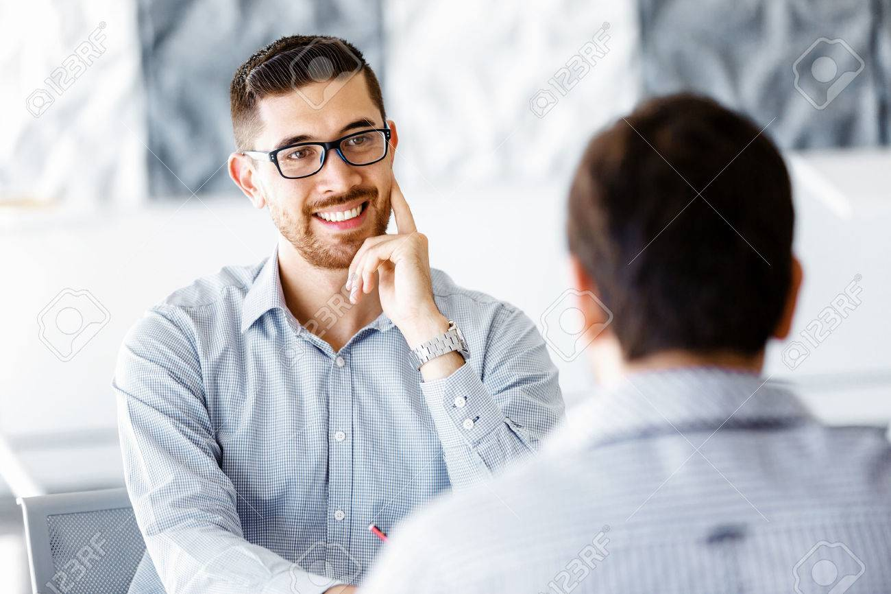 Two handsome businessman in office sitting at desk and talking Stock Photo - 54554898