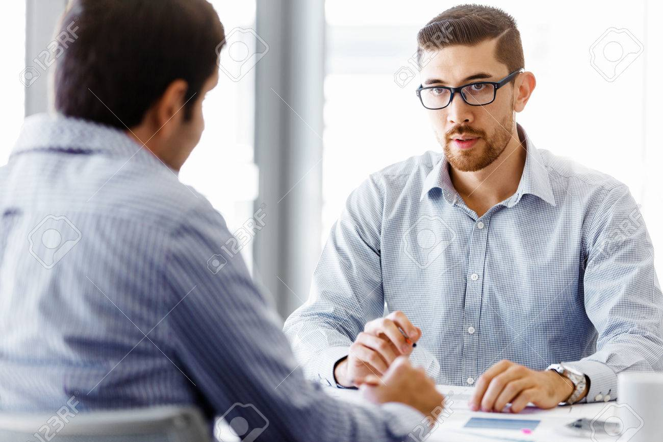 Two handsome businessman in office sitting at desk and talking Banque d'images - 55398150