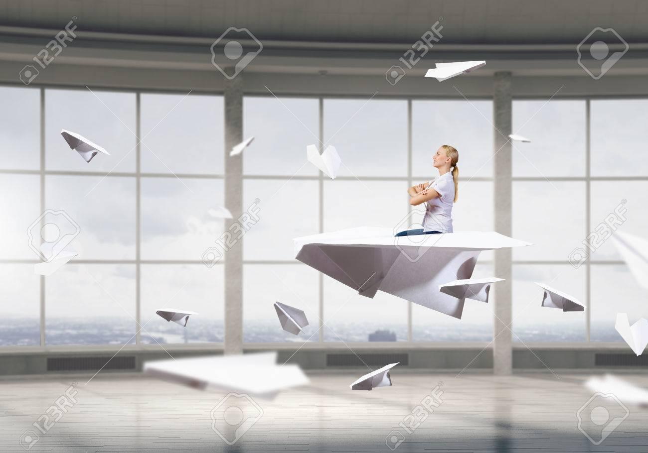 Businesswoman avion de papier volant dans un intérieur moderne de