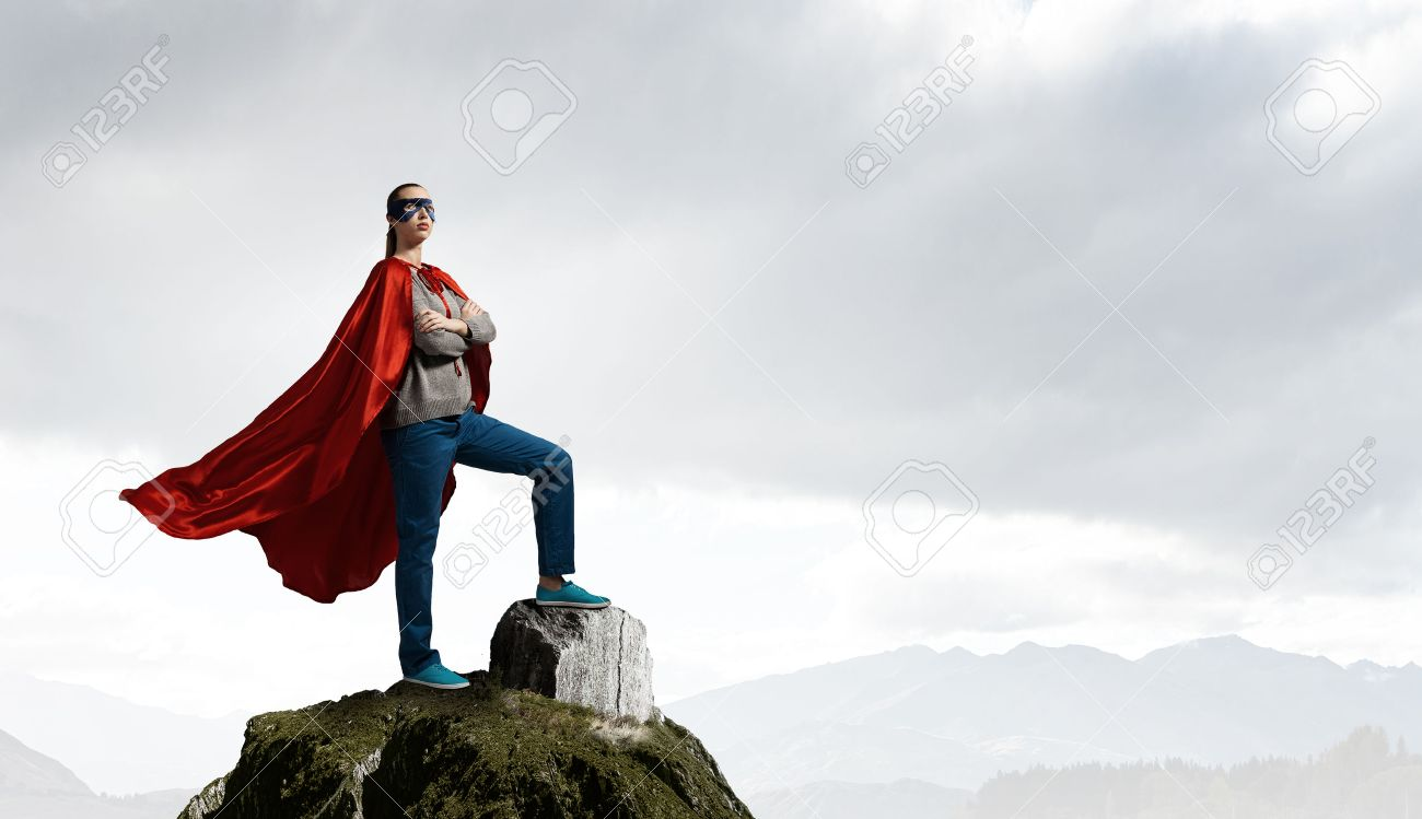 Young confident woman in red cape and mask on rock top Standard-Bild - 57700806