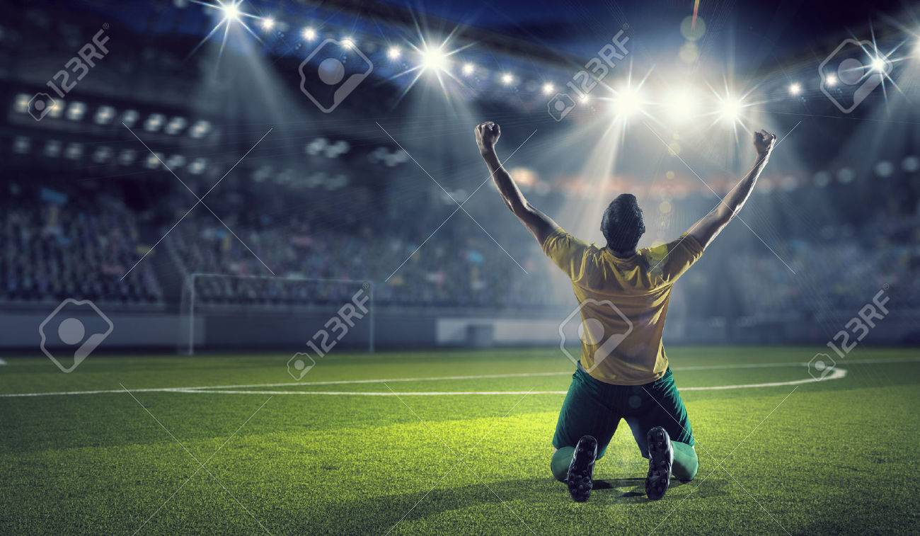 Soccer player celebrating victory while holding win cup - 58144415