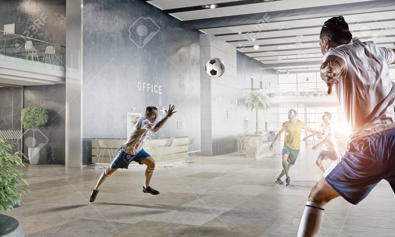 players and businessman playing soccer ball in modern office stock photo 59635696