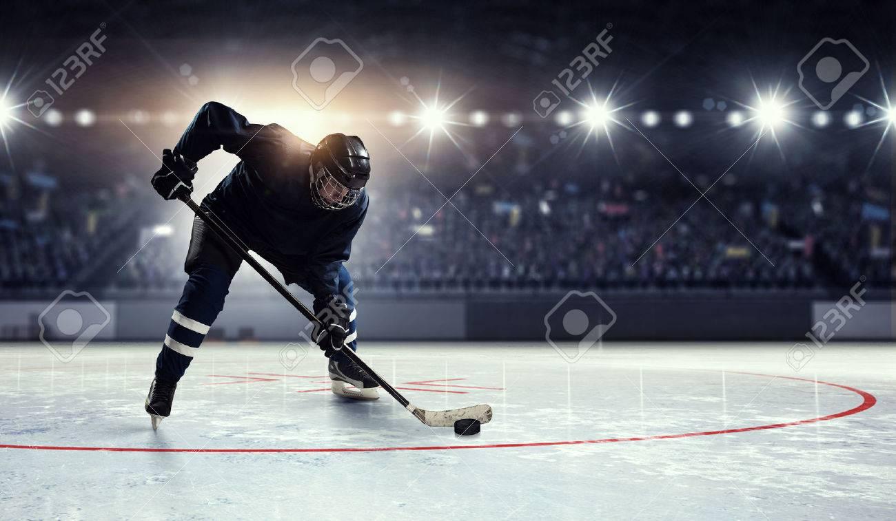 joueur de hockey en uniforme bleu sur la patinoire sous les projecteurs Banque d'images - 60033939