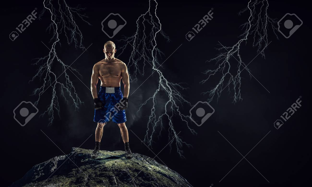 Strong boxer on dark background demonstrating power and endurance