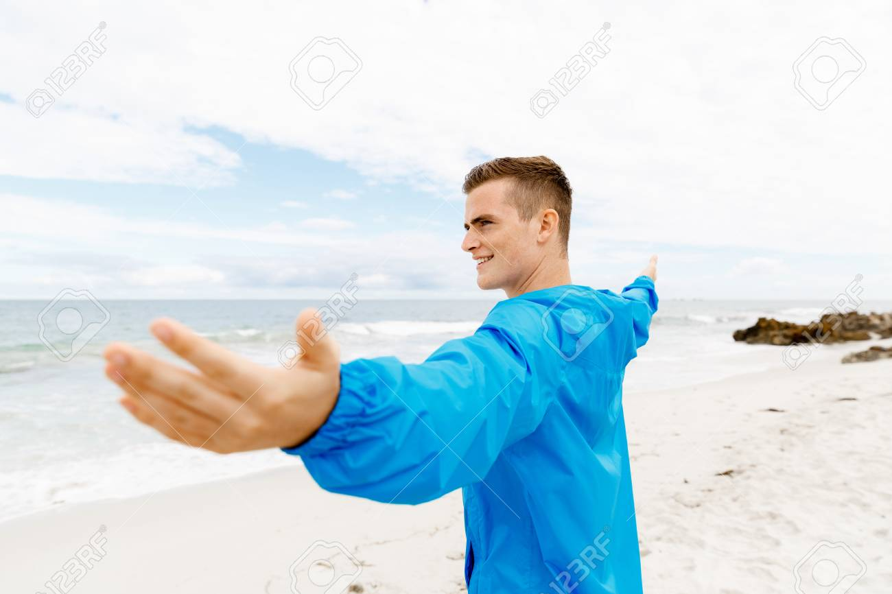 young man in sport wear with outstretched arms standing on beach