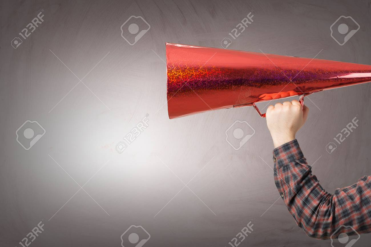 Male hand in checked shirt make announcement in red paper trumpet