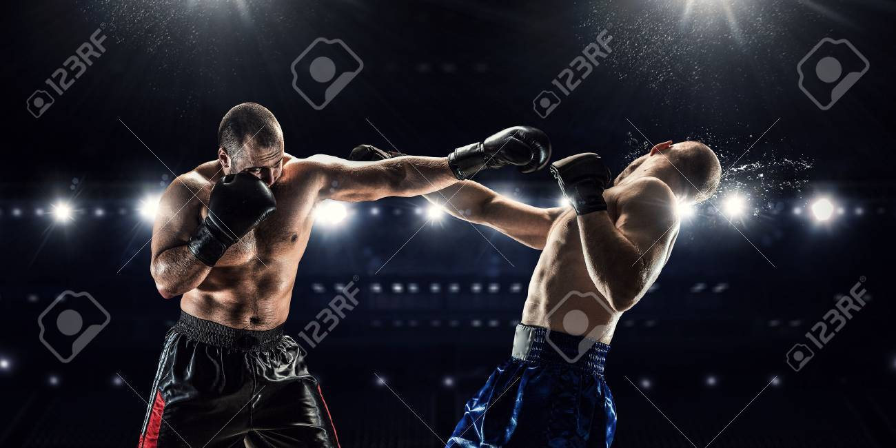Two professional boxers fighting on arena in spotlights Banque d'images - 63350236
