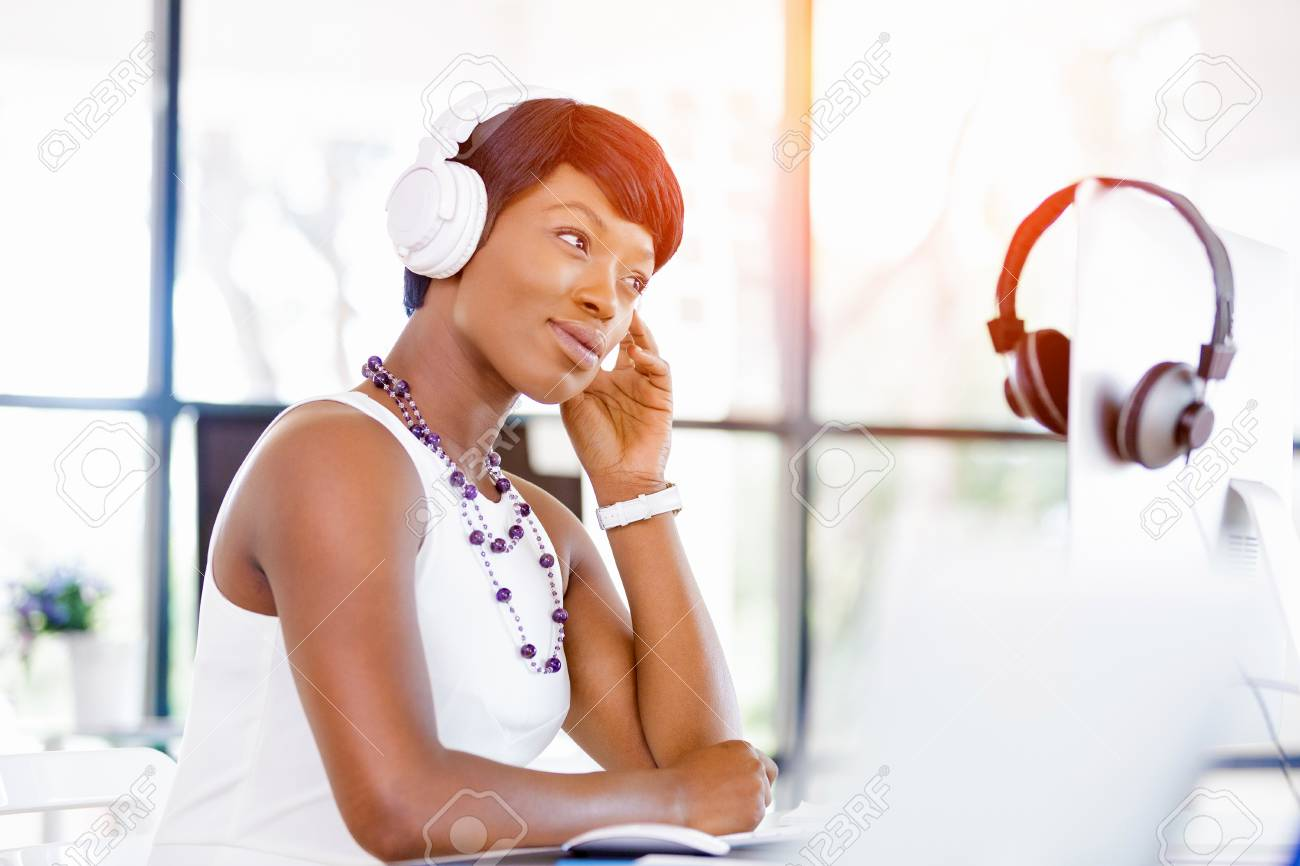 Young beautiful businesswoman listening music in headphones at