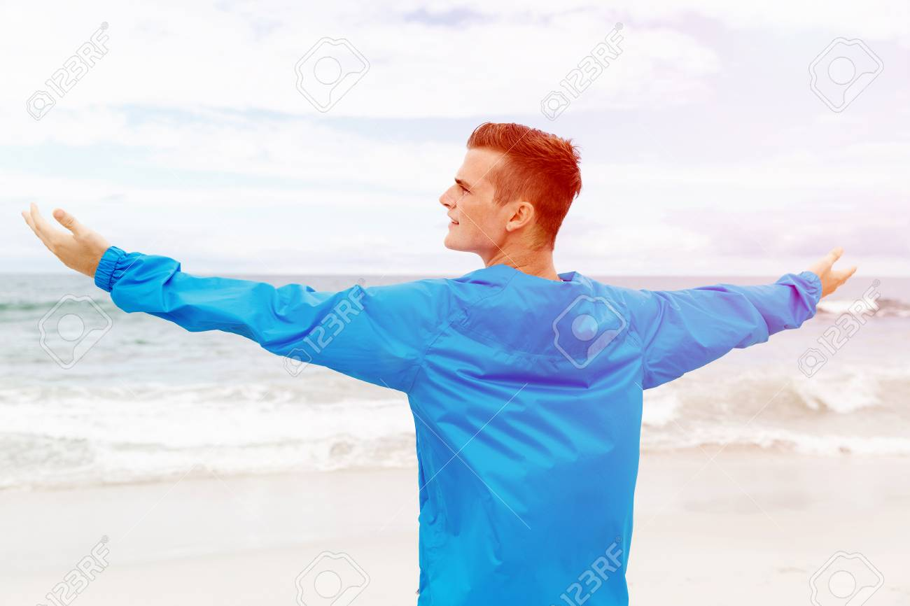 young man in sport wear with outstretched arms stock photo picture