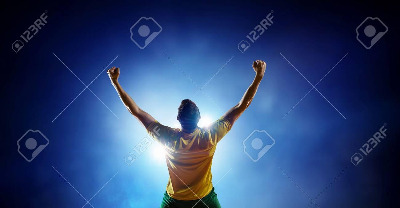 Soccer player at stadium. Mixed media - 100325032