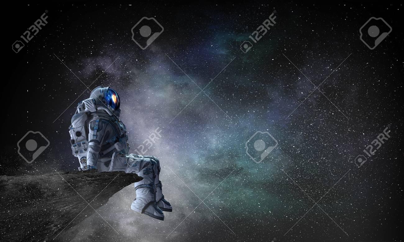 Astronaut sitting on cliff edge against dark starry sky. Mixed media - 102156373