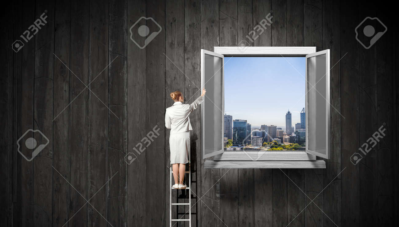 Businesswoman standing on ladder and reaching up opened window in wall. Mixed media - 137155934