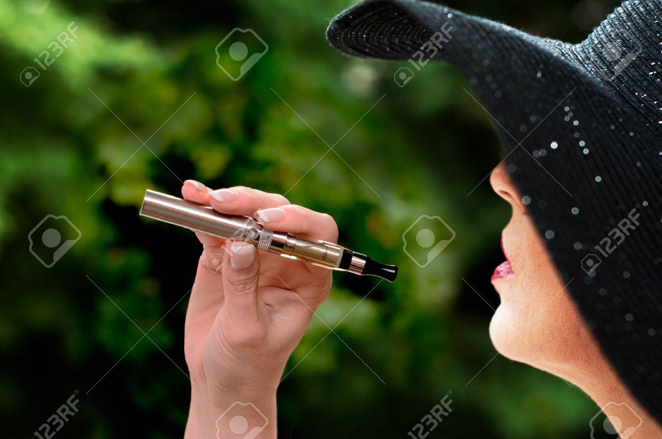 fashion woman with e-cigarette in outdoor - 34535639