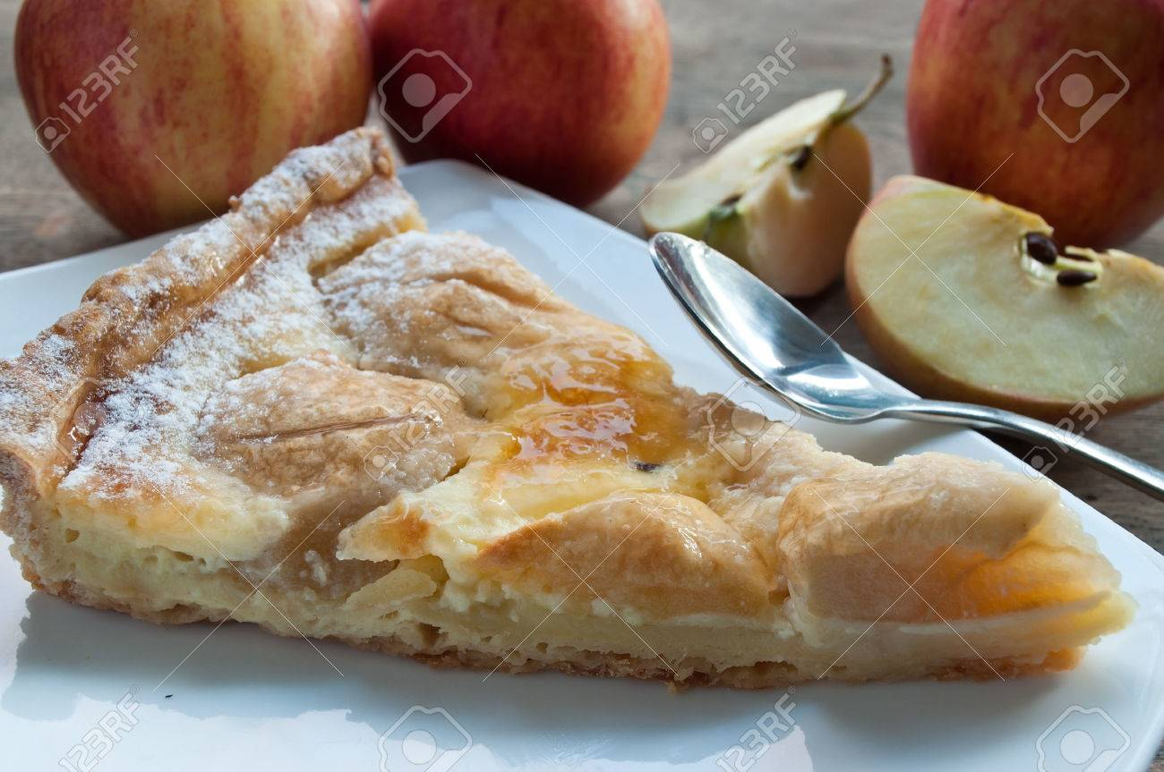 closeup of apple pie with raw apples on wooden table - 49831928