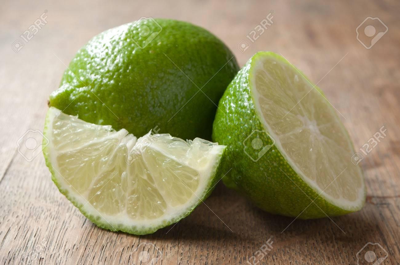 closeup of green lemon on wooden background - 50011664