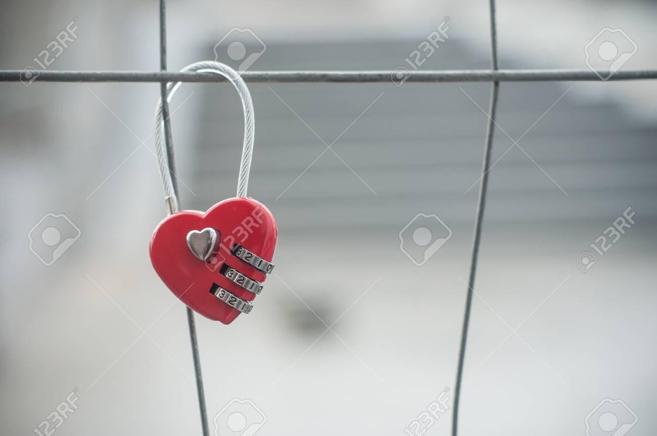 closeup of red padlock in shaped heart on metallic grid - 94299624