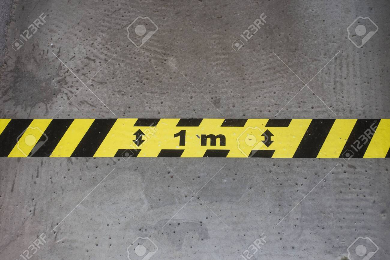 Closeup of yellow and black stripped line on the floor - Social distancing line - 149980103