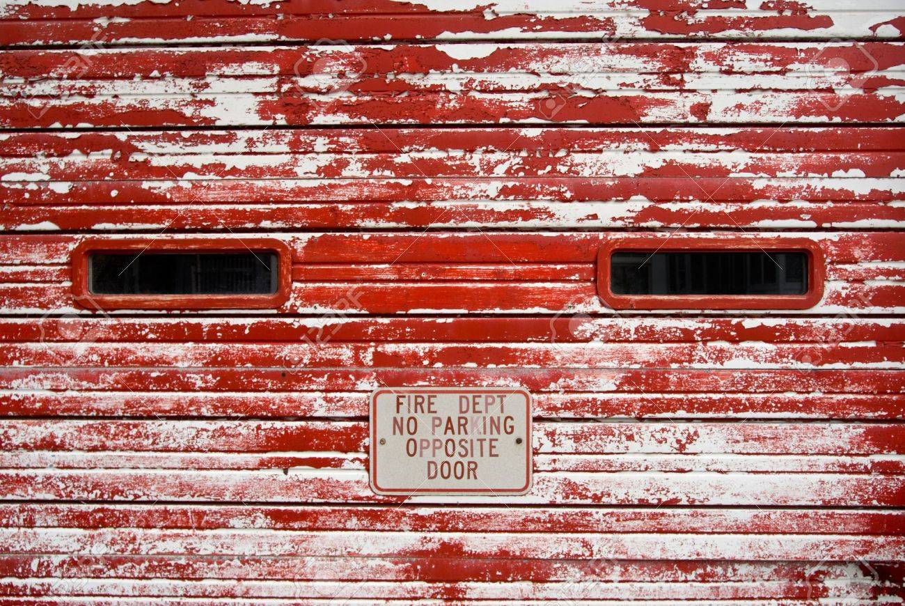 Vintage fire department wooden garage door with peeling, faded red paint Stock Photo - 3108274
