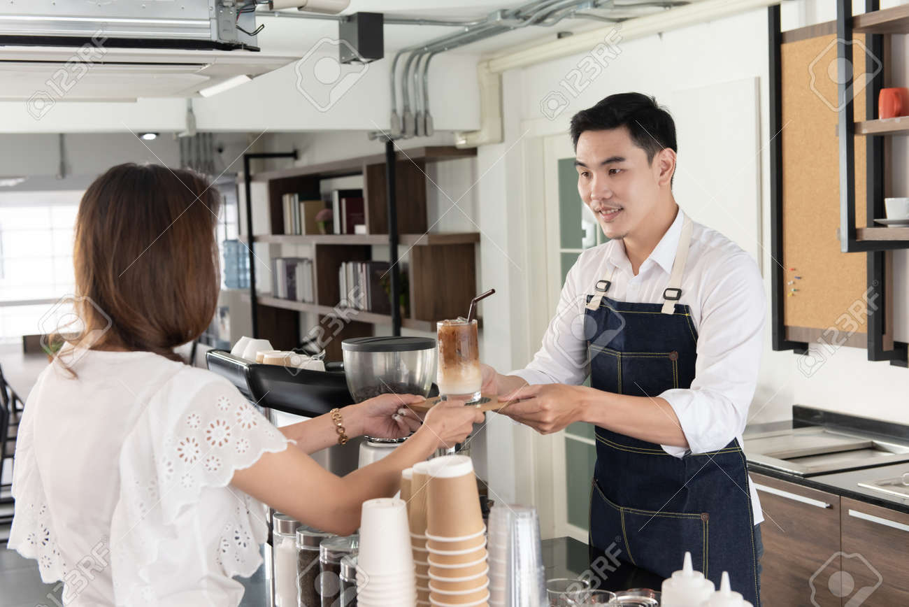 Smiling Asian barista man holding cup of ice beverage to show the customers in the coffee shop - 158942687