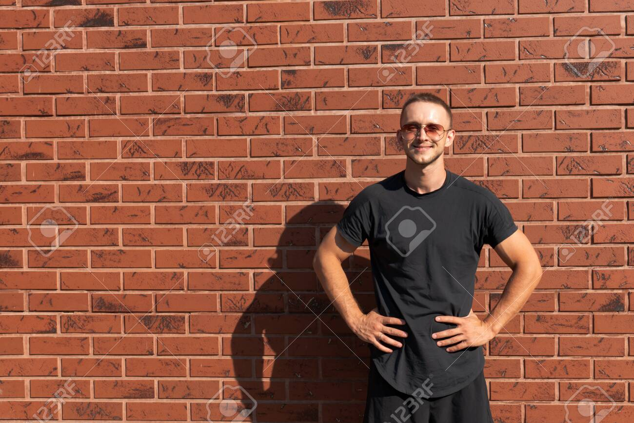 Happy attractive young man in sunglasses, dressed in black t-shirt standing with hands on a belt, red brick wall on the background - 134939401