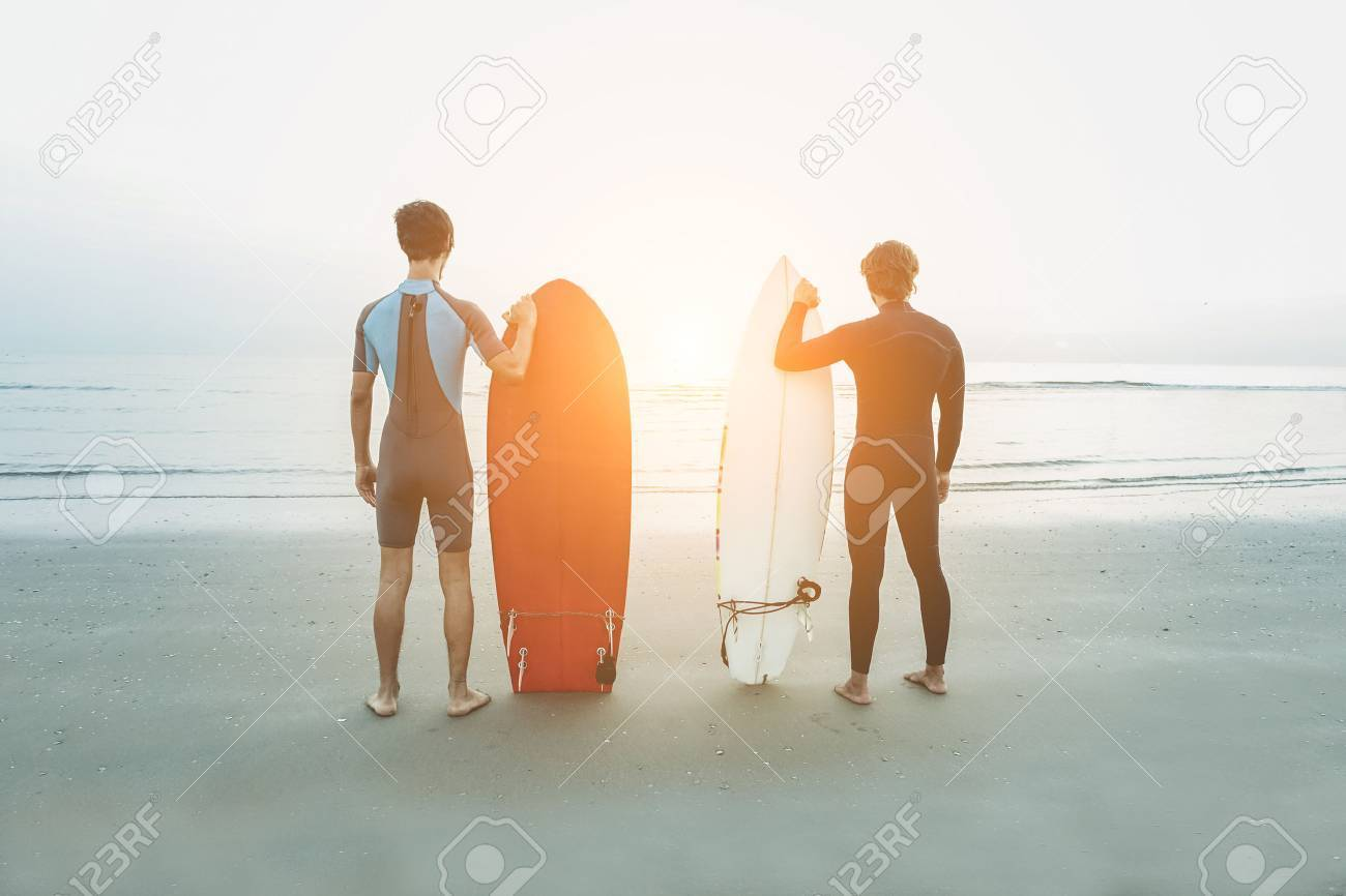 Young surfers waiting the waves on beach with sunlight in background - Sport friends preparing looking the horizon ready for for surfing - Extreme sport and vacation concept - Soft focus on them Stock Photo - 72302318